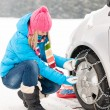 Woman putting winter tire chains car wheel — Stock fotografie
