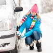 Woman putting winter tire chains car wheel — Stock Photo #13814378