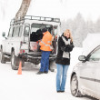 Mechanic helping woman with broken car snow — Stock Photo #13814406