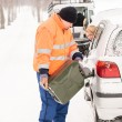 Man filling woman car gas winter assistance - Stockfoto