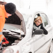 Man repairing woman's car snow assistance winter - Stock Photo
