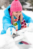 Woman brushing snow from car windscreen winter — Stock Photo