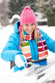 Woman wiping car windshield using brush snow — Stock Photo