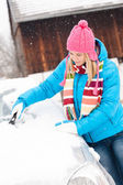 Woman cleaning snow car hood with scraper — Stock Photo
