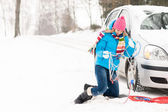 Woman with winter car tire chains snow — Stock Photo