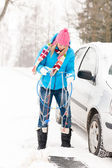 Woman having problems with car snow chains — Stock Photo