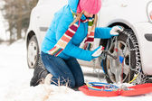 Woman putting chains on car winter tires — Stock Photo