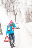 Woman with warning triangle car snow breakdown — Stock Photo