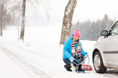Snow tire chains winter car woman trouble — Stok fotoğraf