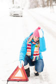 Woman put warning triangle car breakdown winter — Stock Photo