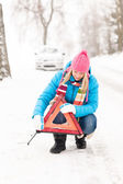 Woman put reflector triangle car breakdown winter — Stock Photo