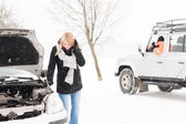 Woman looking under broken car hood snow — Stock Photo