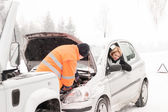 Man repairing woman's car snow assistance winter — Stock Photo