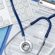 Stethoscope laying over doctors emergency report - Stock Photo