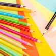 Color pencils on colorful papers close-up - Stock Photo