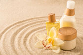 Spa body product on sand orchid flower — Stock Photo