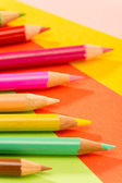 Color pencils on colorful papers close-up — Stock Photo