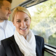 Stock Photo: Woman smiling in train man selective focus