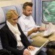 Woman with laptop man newspaper in train — Stock Photo