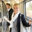 Stock Photo: Womsmiling in train hall with luggage
