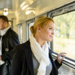 Woman looking out the train window traveling — Stock Photo #17417229