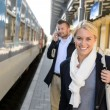Woman smiling in train station man phone — Stock Photo