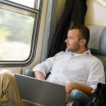 hombre mirando el portátil de ventana de tren — Foto de Stock
