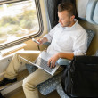 Man texting on phone holding laptop train — Stock Photo