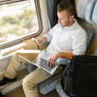 Man texting on phone holding laptop train - Stock Photo