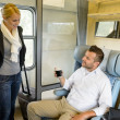 Woman getting in train compartment with man - ストック写真