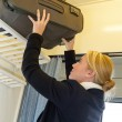 Woman putting her luggage on train grid - Stock Photo