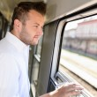 Man looking out the train window smiling - Stockfoto