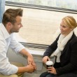 Woman and man traveling with train talking - Stockfoto
