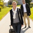 Woman leaving with baggage man walk behind — Stock Photo