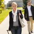 Woman arriving in park with baggage man — Stock Photo
