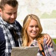 Couple together on holiday with map happy — Stock Photo