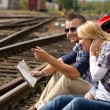 Man pointing direction with map on railroad — Stock Photo