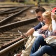 Couple looking at map sitting on railroad — Stock Photo
