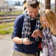 Man showing woman pictures on digital camera — Stockfoto