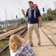 Man waving to woman sitting on railroad - Stock Photo