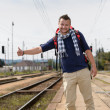 Man hitchhiking on railroad train station smiling — Stock Photo #17417577