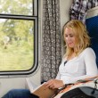 Womreading book in train smiling commuter — Stockfoto #17417685