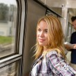 Woman looking out the train window smiling — Stockfoto