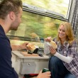 Couple eating sandwiches on train traveling smile — Stock Photo