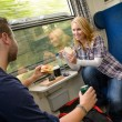 Stock Photo: Couple traveling by train eating sandwiches hungry