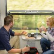 Man looking out the train window eating — Stock Photo