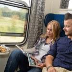 Couple traveling by train reading magazine smiling — Stock Photo