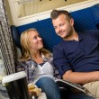Couple smiling at each other in train - Stock Photo