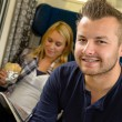 Man smiling sitting on train woman sandwich — Stock Photo