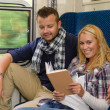 Couple traveling by train woman reading smiling — Stock Photo